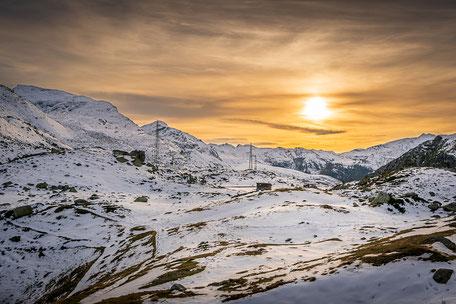 Tiefstehende Sonne über der verschneiten Landschaft auf dem Julierpass