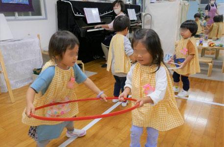 2歳児が、フープを使ったリトミックで2人組になって活動しています。