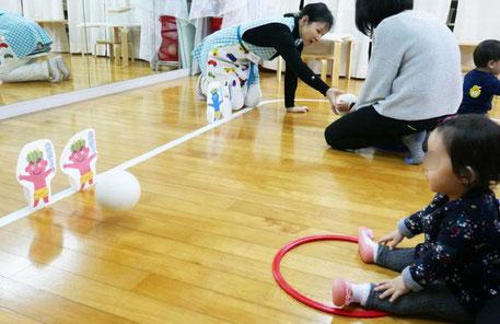 モンテッソーリの活動で0~1歳児がおかあさまといっしょにボールを転がして鬼のピンを倒すボール遊びをしています。