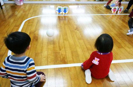 モンテッソーリの活動で2才児がボール遊び。鬼のピンをめがけてボールを投げて、鬼を倒します。