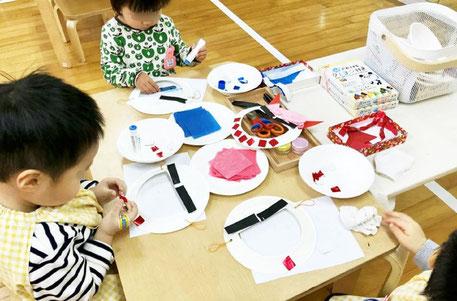 モンテッソーリの活動で2才児が鬼のお面を製作。紙をハサミで切って、土台にノリで貼っています。