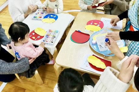 モンテッソーリの活動で0~1歳児が鬼のお面を親子で楽しく作っています。