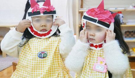 モンテッソーリの活動で2歳児が製作した鬼のお面をかぶりました。かわいい鬼さんができました。