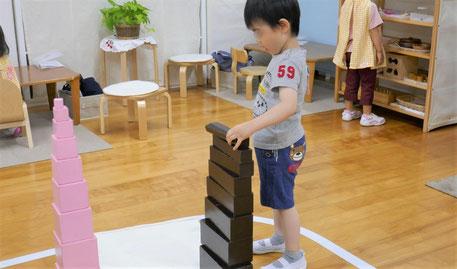 2歳児がモンテッソーリの感覚教具を使って活動をしています。