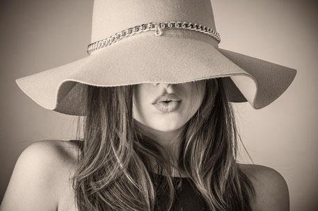 lange, blonde Haare, Kopf von einer Frau, Gesicht halb mit einem großen Hut verdeckt.
