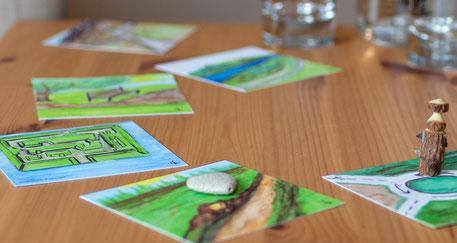 Bild zeigt Karten mit gezeichneten Bildern von Wegen, die auf einem Tisch aufgelegt sind. Auf einer Karte liegt ein Herz aus Stein, auf einer anderen steht eine Holzfigur.