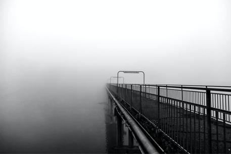 Un ponte che si perde, scompare nella nebbia del fiume.