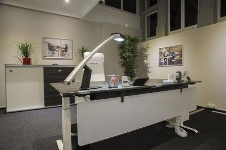 Großer Schreibtisch und Arbeitsplatz im Büro mit verschiedenen Büromöbeln