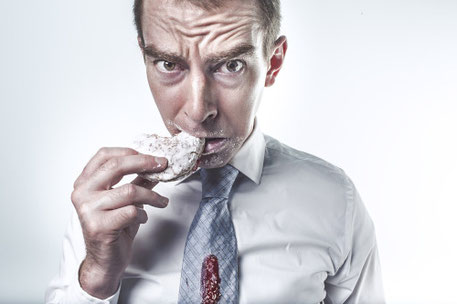 Foto eines gestressten Mannes, der im Büro hungrig Fast Food verschlingt und damit ein Leaky Gut Syndrom begünstigt.