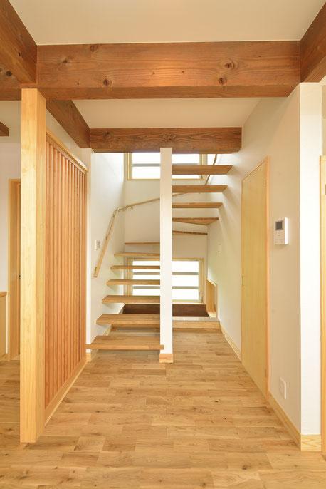 大きな吹抜けの家の階段は奥の窓から光を感じる
