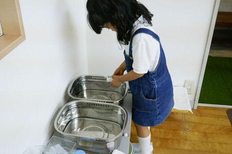 モンテッソーリの活動で、幼稚園児が日常生活の活動としてきゅうりを切る活動に取り組みました。食べ終わったら使ったお皿とフォークを自分で洗います。