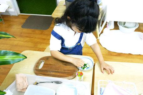 モンテッソーリ活動の日常生活の練習で、幼稚園児が自分で切ったきゅうりに塩をかけています。