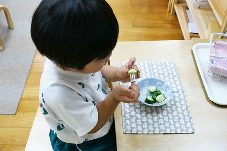 幼稚園児がモンテッソリ-活動での日常生活の練習できゅうりを切る活動をしました。切ったきゅうりを自分で食べます。