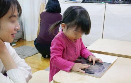 モンテッソーリの個別活動で1歳児が絵本を楽しみ、お母さまが静かに見守っています。