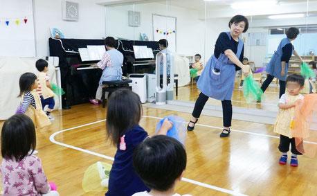 母子分離2歳児がリトミックで、ピアノにあわせてスカーフを振っています。みんなの動きがそろってとてもきれいです。