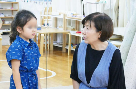 モンテッソーリの個別活動で、幼稚園児に活動のしかたについて説明をしています。