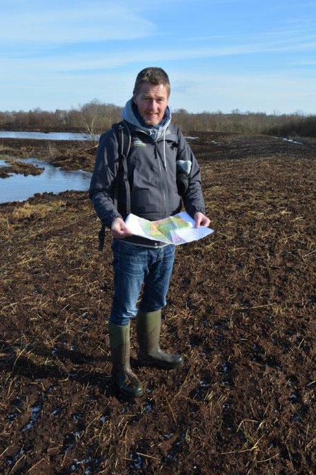 Mann steht im Moor mit einem Plan in der Hand
