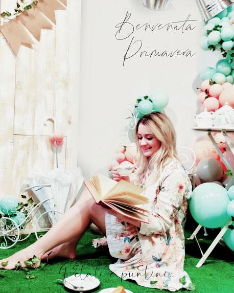 ragazza che legge libro e beve il thè circondata da palloncini e decorazioni primaverili