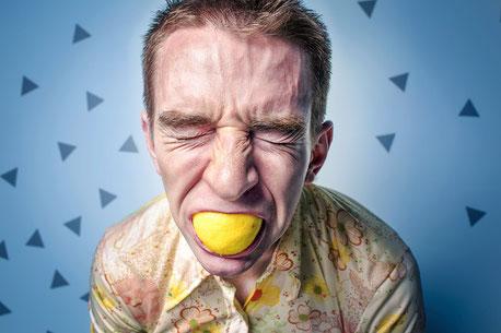 Mann beisst in halbe Zitrone und verzieht das Gesicht, Stress und Entspannung, EMDR, Trauma-Therapie, PTBS, Rosacea, Neurodermitis, Psoriasis, Psychotherapie
