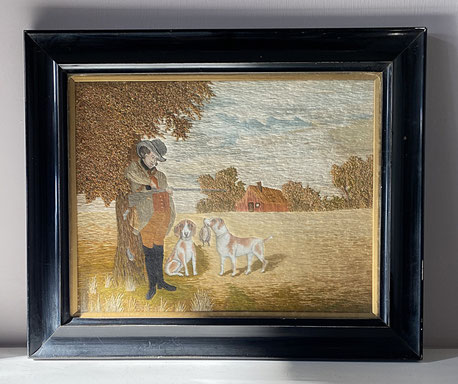 Hunter with gun dogs.  Early 20th century fine silkwork in ebonised frame.