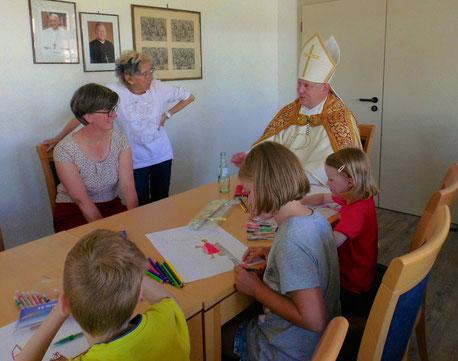 Zusammen an einem Tisch sitzen der Nikolaus, drei Kinder, die am Malwettbewerb teilnehmen und Insel-Seelsorgerin Susanne Wübker