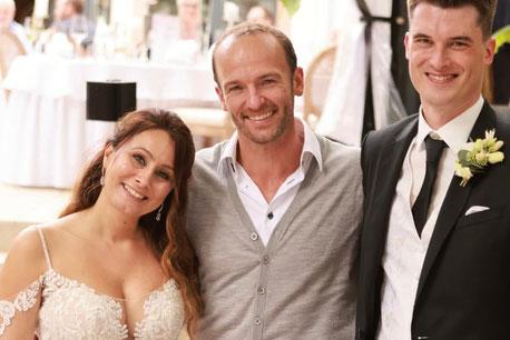 Glückliches Brautpaar mit Sänger