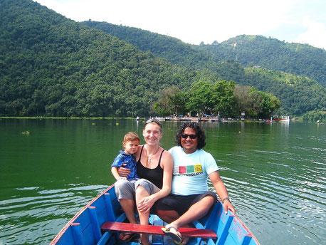 Familie im Boot, dahinter Wald mit Aufstieg zur Shanti Stupa. Foto: Lene Löwenherz
