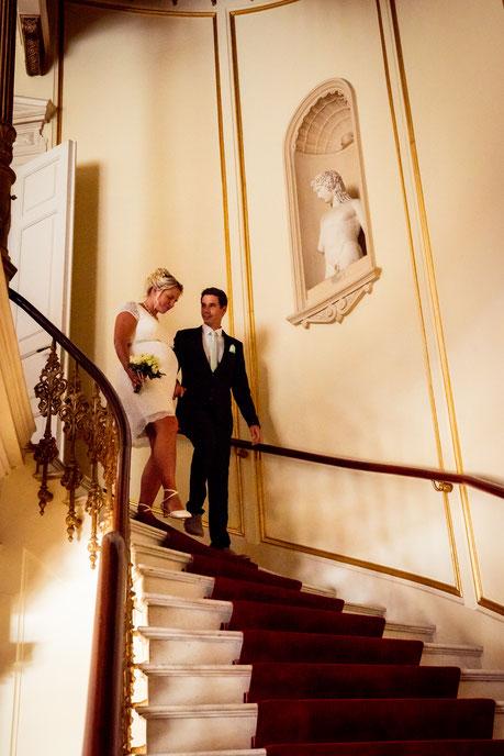 Christopher und Ivonne kommen eine prunkvolle Treppe herunter.