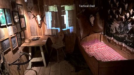 Die Widererstube im Bergbauernmuseum. Unter dem Tisch ist ein verstecktes Gewehr montiert. Links an der Wand sind die Geschichten der wichtigsten Wilderer kurz erzählt.