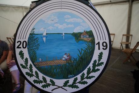 Die noch intakte Zielscheibe für das Schützenfest 2019 zeigt in der Mitte ein gemaltes Bild vom Dümmer-See mit einem Steg  und einem sitzenden Pärchen darauf im Vordergrund, Wasser dahinter und am leicht bewölkten Horizont zwei Segelschiffe.