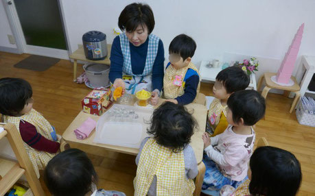 母子分離2才児がモンテッソーリの活動で、本物のみかんを絞ってジュースをつくる活動をしています。