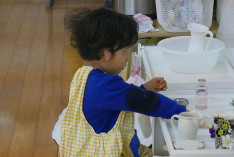 モンテッソーリの活動で2才児が生花の活動に集中して取り組んでいます。