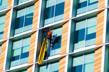 Ein Fensterputzer seilt sich an der Fassade eines bunten Hochhauses ab