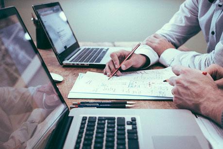 Zwei Personen sitzen an Laptops mit Papierdokumenten vor sich
