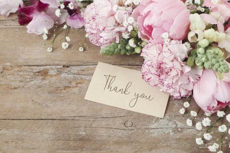 木製のテーブルに無造作に置かれたピンクのチューリップとカーネーション。「ありがとう」と英語で書かれた手書きのメッセージカード。