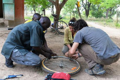 Personne accroupi en train de réparer une roue de vélo, 2 Béninois et 2 Français