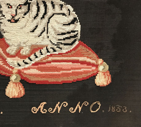 Naive woolwork of a cat on a plush cushion