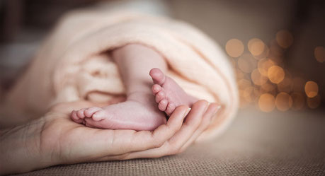 Newborn Babyfüsse die gehalten werden von den Händen der Mutter fotografiert von der Schweizer Familien Fotografin Monkeyjolie