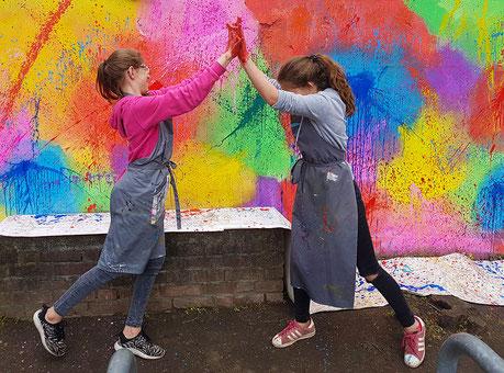 2 kinder amüsieren sich prächtig beim klecksen mit Farben bei der gestaltung einer Mauer in einem Kunstprojekt in der Schule