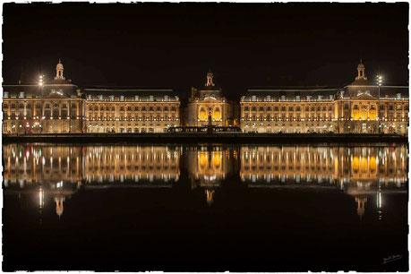 Place de la Bourse à Bordeaux, de nuit, devant le miroir d'eau, avec le reflet dans la Garonne à mareé haute; et le tram à l'arret