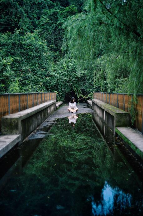 Frau im Meditationssitz auf einer Brücke im Urwald