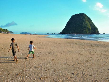 Spelen op het uitgestrekte strand van Red Island beach op oost Java