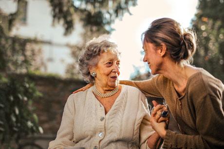 Junge Frau legt den Arm um eine Seniorin, beide lächeln und sehen sich an