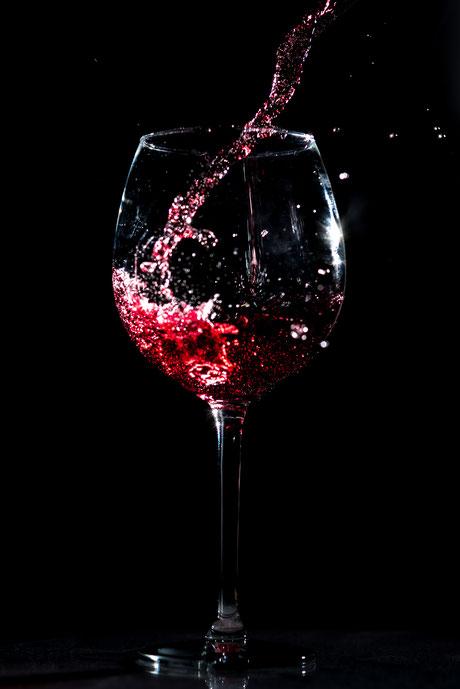 Rotwein spritzt ins Weinglas