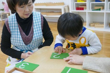 1才児がモンテッソーリ活動で砂文字盤を使って数字を練習をしています。