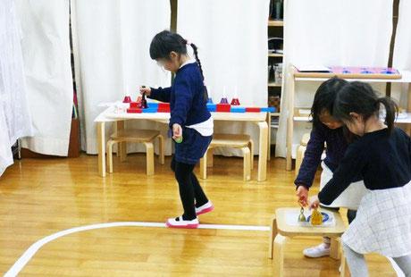 モンテッソーリの活動で、選んだ物を持ったり頭の上にのせて線上を歩行する線上遊戯の練習を幼稚園児が集中して行っています。