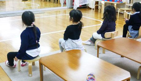 リトミックの時に、幼稚園児クラスの生徒が背筋を伸ばして姿勢良くイスに座っています。っています