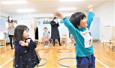 2歳児がリトミックで、並んだフープをピアノに合わせてジャンプしました。