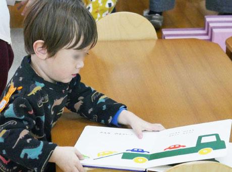 モンテッソーリの個別活動で、1才児がお気に入りの車の絵本を見ています。