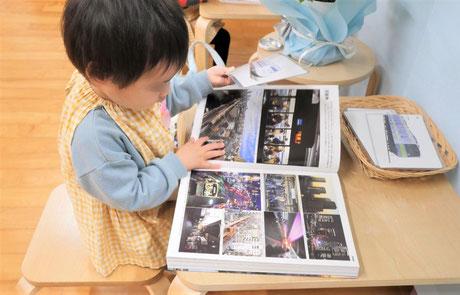 2歳児がモンテッソーリの個別活動で電車を図鑑で確認しています。
